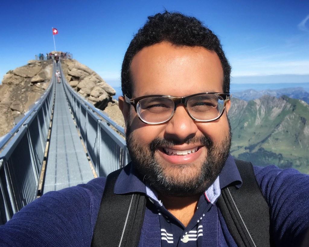 Me on a suspension bridge between two mountain peaks