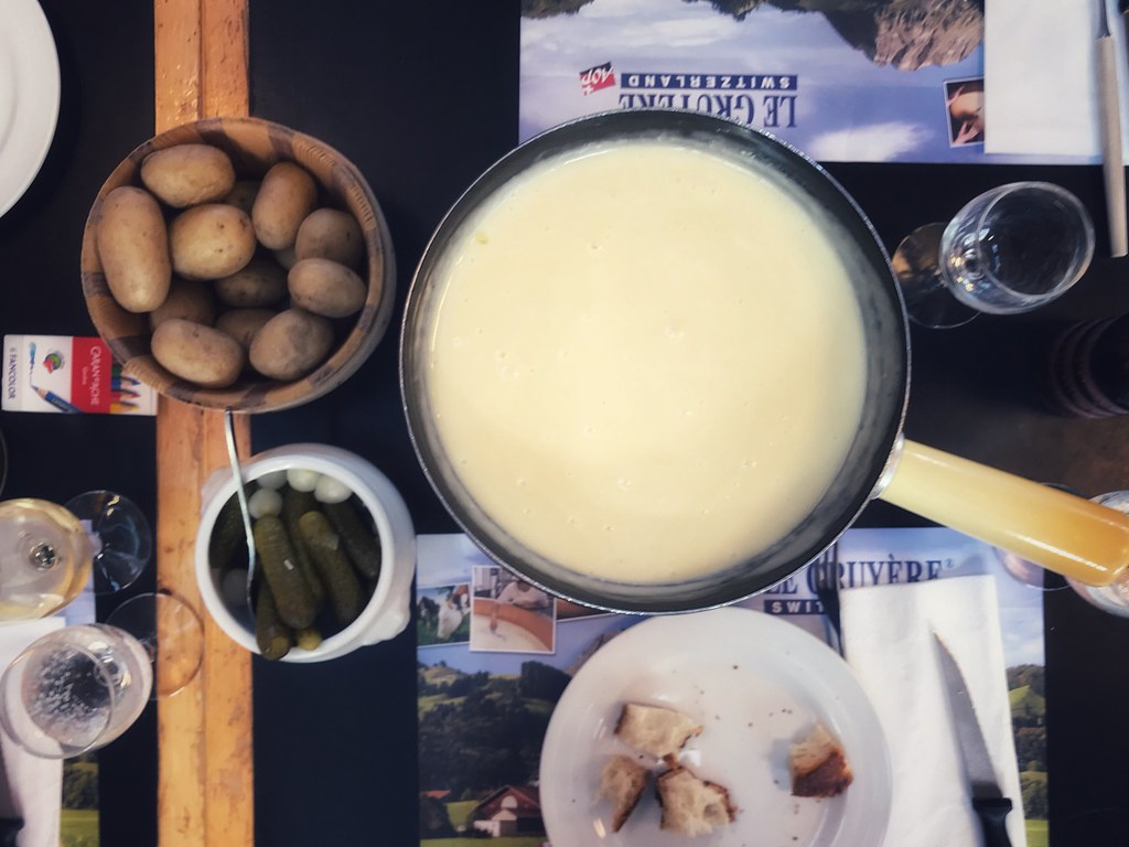Fondue pot with pickles and potatoes on the side