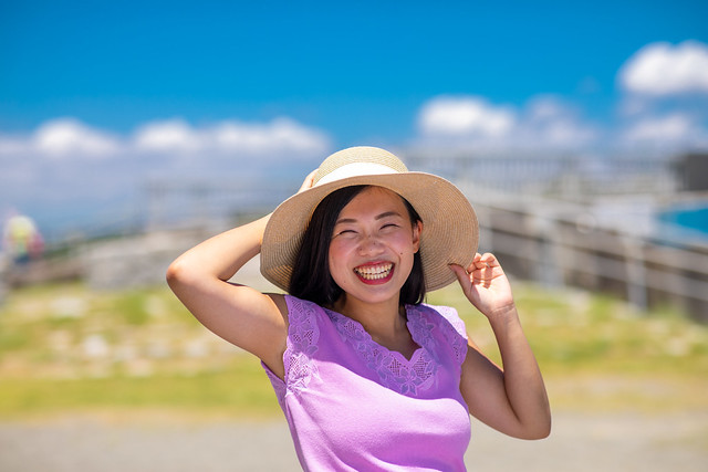 Portrait of happy young woman with straw hat in summer