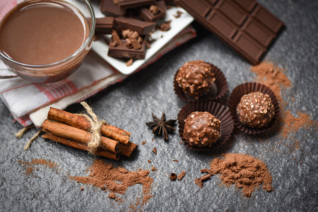Chocolate bar and spice on the dark background / chocolate ball and chocolate pieces chunks chips powder candy sweet dessert for snack with hot cocoa drink in glass mug , selective focus