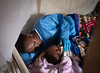 Kavira Langa Jemima, an Ebola survivor, puts six-month old Josue to bed at a nursery. Josue, whose mother contracted Ebola, has been separated from her while she undergoes treatment in isolation. Unfortunately, she has passed away and his father is receiving treatment.   The children at the nursery are monitored for signs of the virus and receive daily medical check-ups and nutritional assistance, and are taken to see their mothers from a safe place. They also receive love, emotional and psychosocial support from Ebola survivors like Jemima, who have been cured and are, thus, no longer susceptible to the disease.  ©2019 UNICEF/Guy Hubbard. All rights reserved. Licensed to the European Union under conditions.