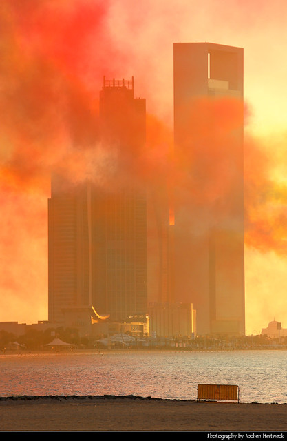 Etihad Towers and ADNOC Headquarters seen through the smoke shortly after the end of the National Day Air Show, Abu Dhabi, UAE