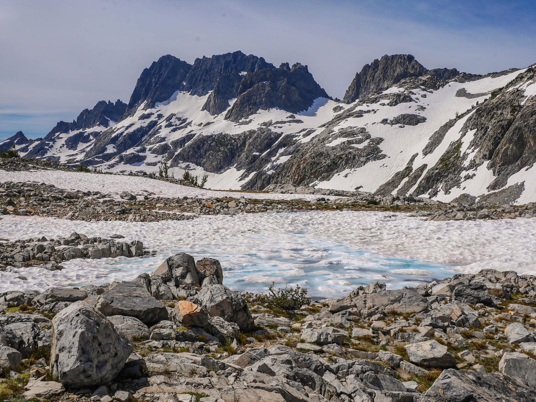 Terrifying snowfield melting into a tarn