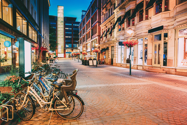 Helsinki, Finland. Bicycles Parked Near Storefronts In Kluuvikatu Street. Night View Of Kluuvikatu Street In Kluuvi District In Evening Or Night Illumination