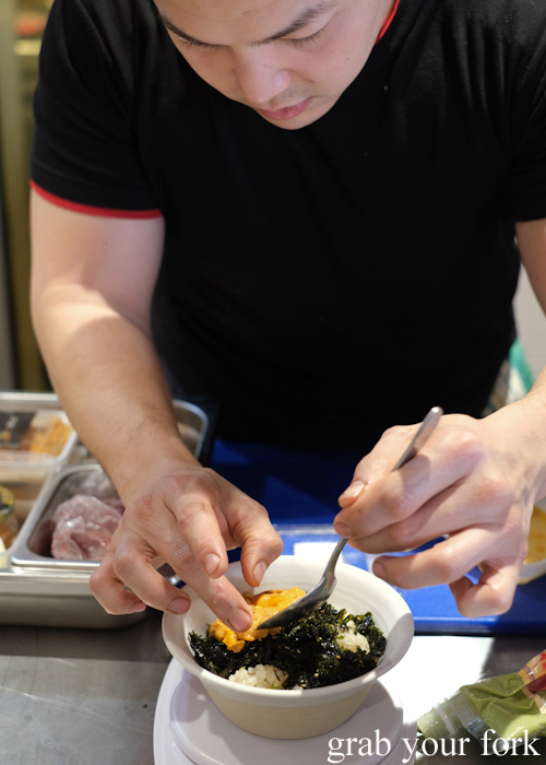 Chef plating up Hokkaido uni sea urchin to our rice bowl at Dopa by Devon in Darling Square Sydney