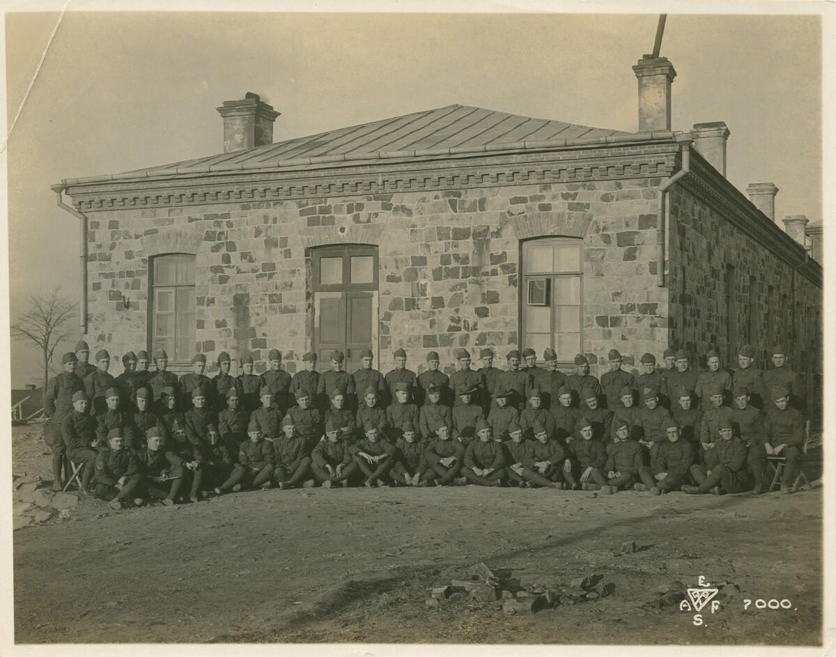 Портрет большой группы людей в форме перед каменным зданием