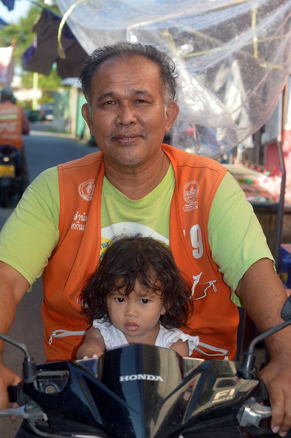 motorcycle taxi driver and his granddaughter