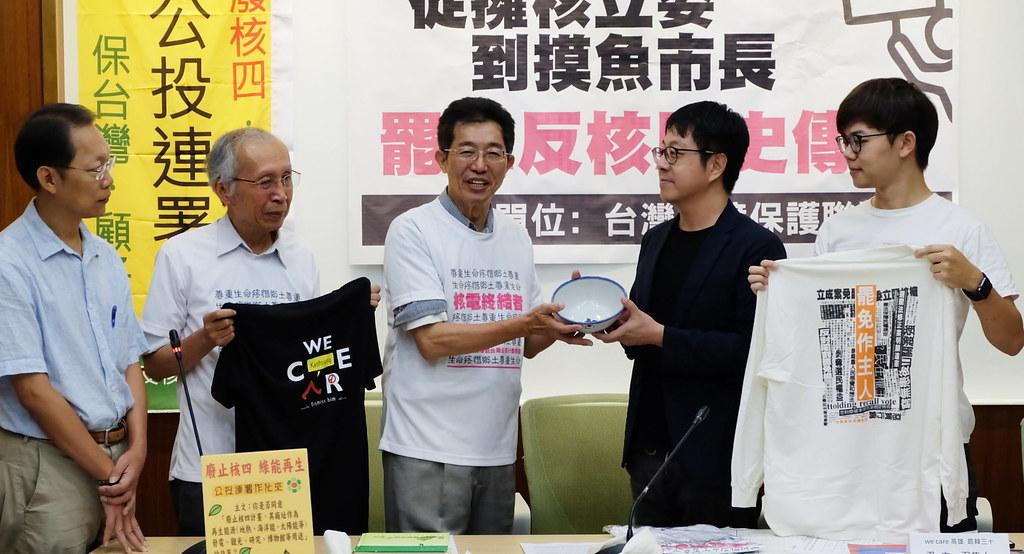 環保聯盟會長與高雄廢合行動互贈T恤,劉志堅(左三)接下尹立(右二)與台灣基進(右一)合贈的警示碗,代表韓國瑜「吃碗內、看碗外」。攝影:陳文姿