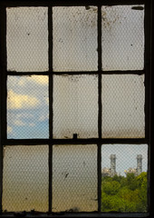 Window frames clouds and smokestacks perfectly