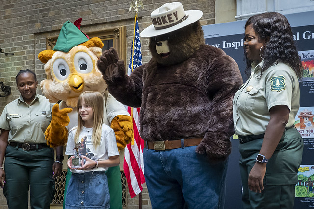 Fourth-grader Penny Atkinson with Smokey Bear and Woodsy Owl