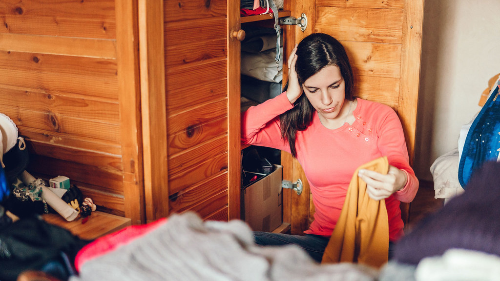 A woman sorting through clothes in a messy room