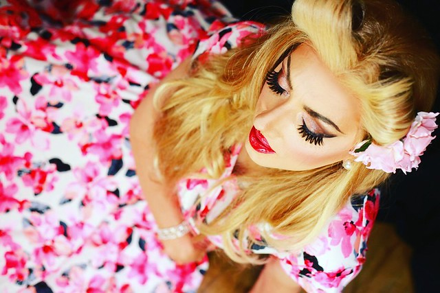 A more arty shot of a girl, the flower in her hair, her gorgeous lashes, her full ruby red lips and her flowing summer floral frock