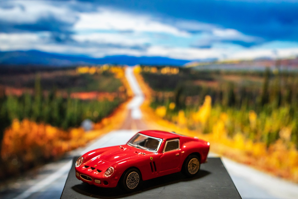 Red Ferrari toy car on platform with scenery background