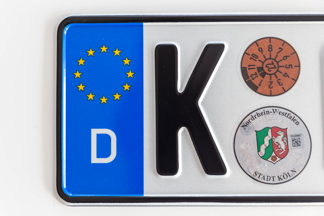 Top view of a German license plate of Cologne, with European stars, on a white surface
