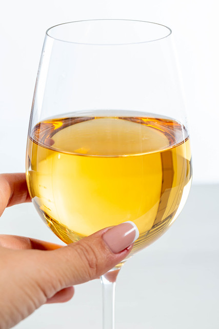 Woman's hand holding a glass of white wine, close-up