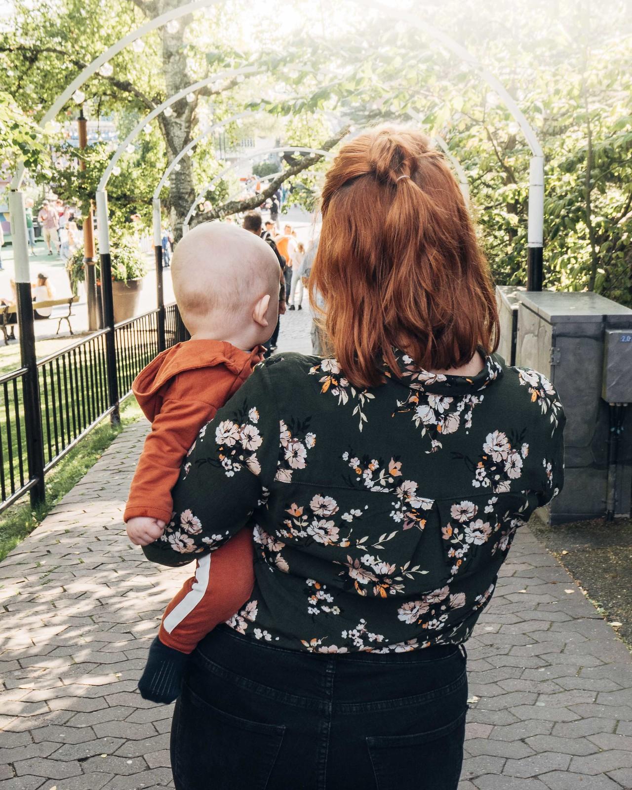 Nainen seisoo vastavaloon lapsi sylissään