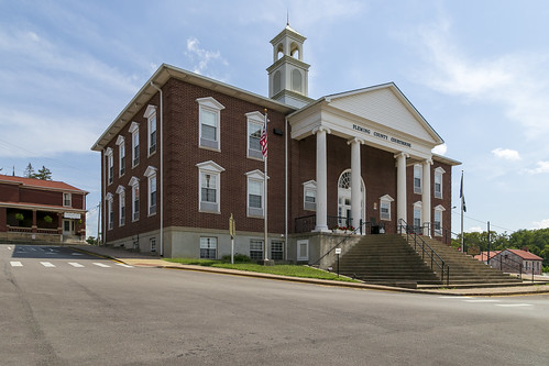 building structure twostory brick flemishbond neoclassical classicalrevival georgianrevival 1954 courthouse flemingcounty kentucky flemingsburg tower cupola pedimented 88windows portico entablature ionic columns capitals volutes street sidewalk hillside clouds