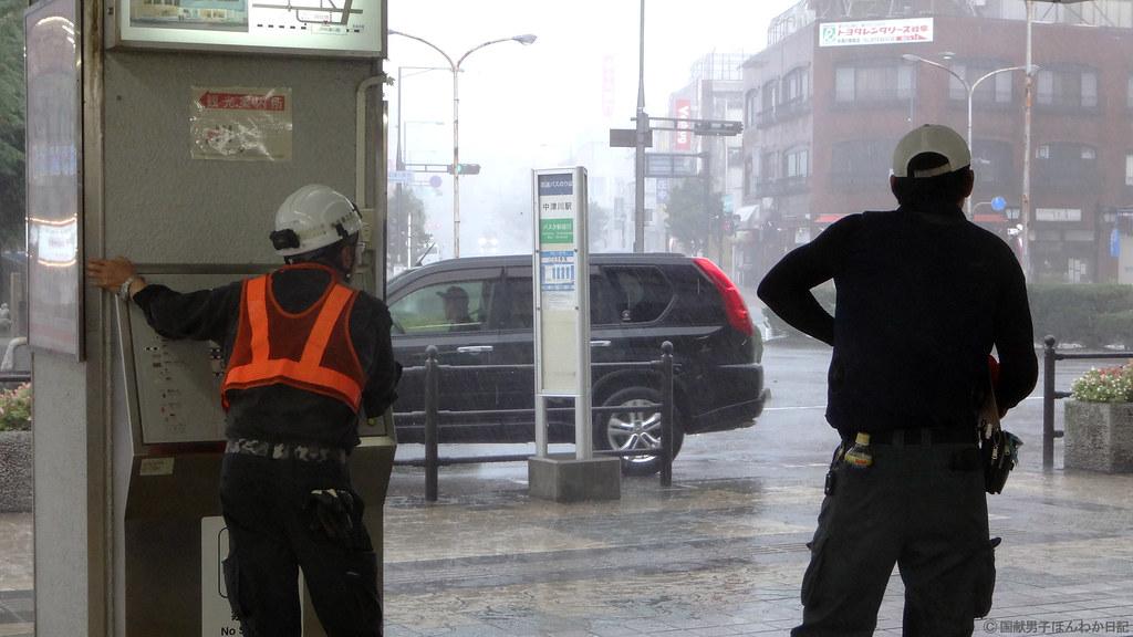 中津川駅では強風に飛ばされないよう柱につかまる人も