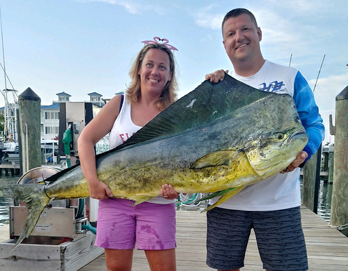 Woman stands with record chidken dolphinfish she caught.