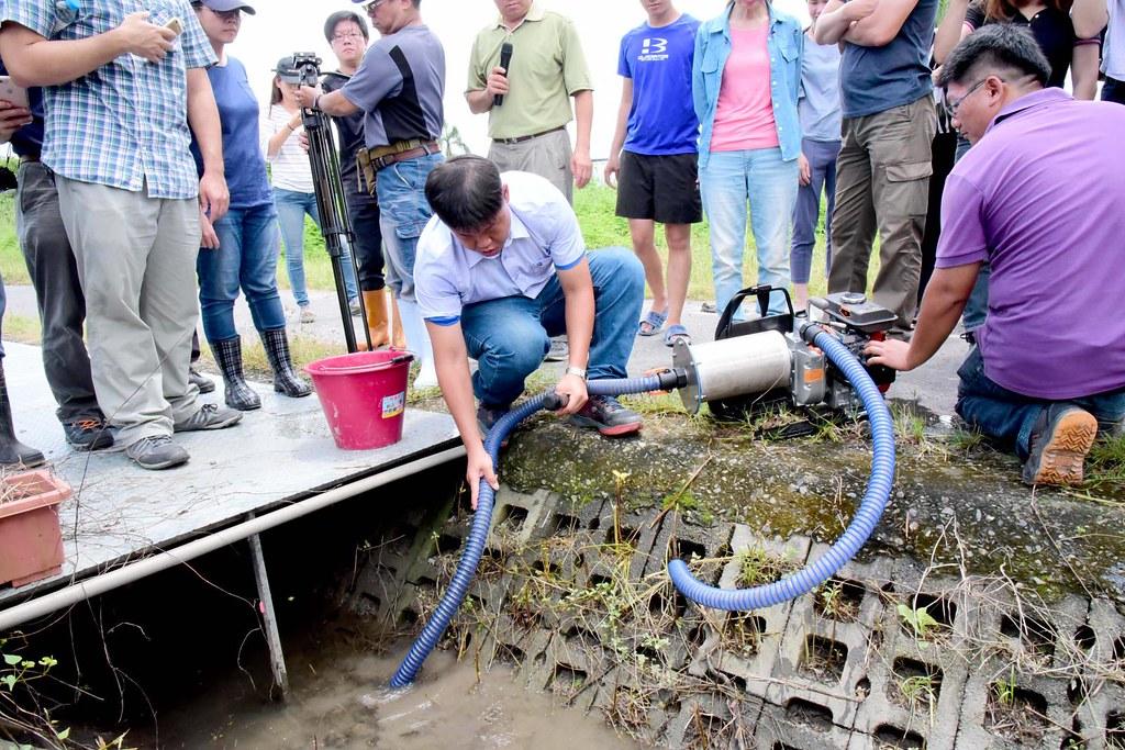 屏科大生機系陳韋誠助理教授於溝渠內使用福壽螺吸塵器