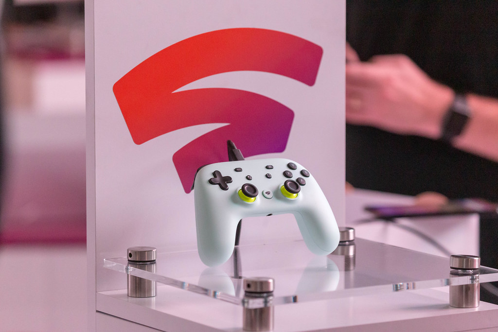 Photo of a Google Stadia controller sat atop a clear pedestal with the Stadia logo behind it.