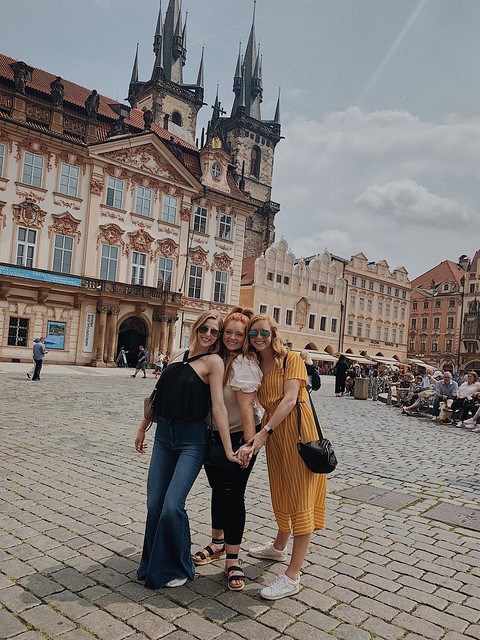 Three students posing in Prague's city square