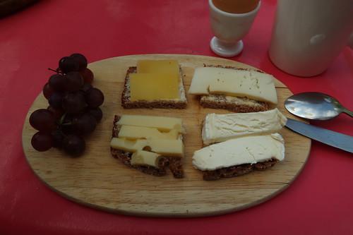 Diverse Käse auf Bio-Brot und dazu dunkle Trauben