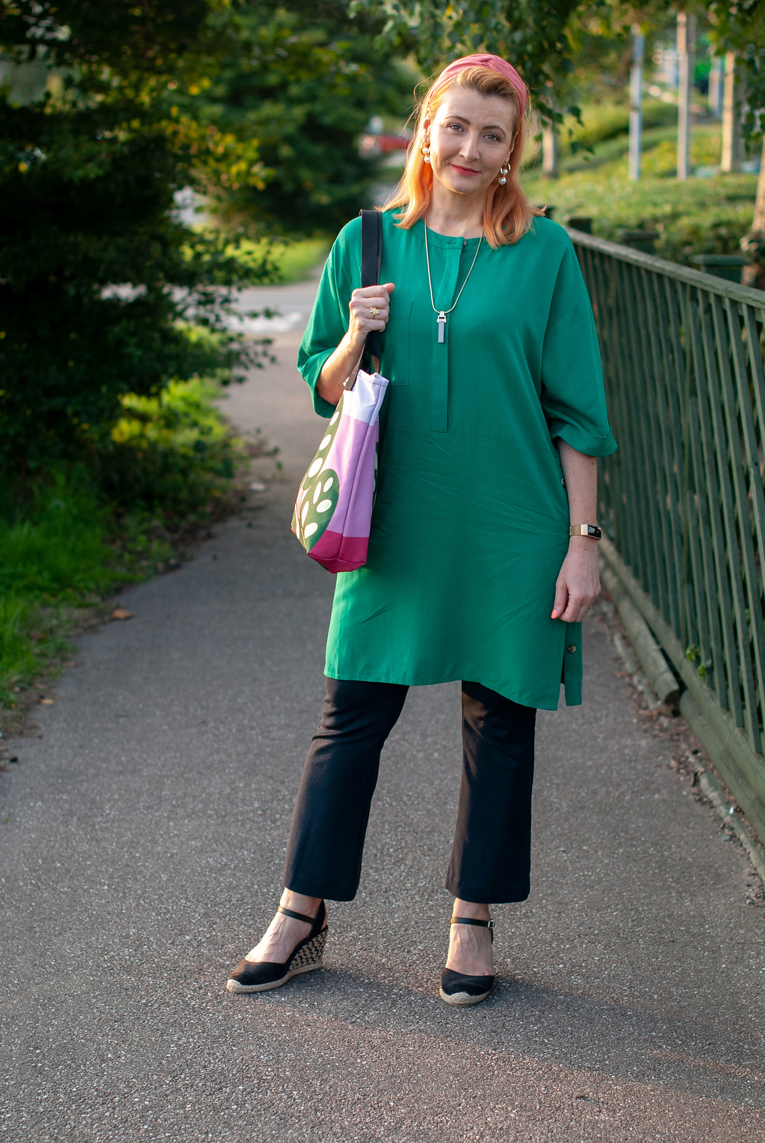 """Wearing a Colour I Don't Normally Wear: Emerald Green"" by Over 40 Blogger Not Dressed As Lamb (outfit of emerald green shift dress over black flare trousers \ black wedge espadrilles \ pink headband \ green on pink tote bag)"