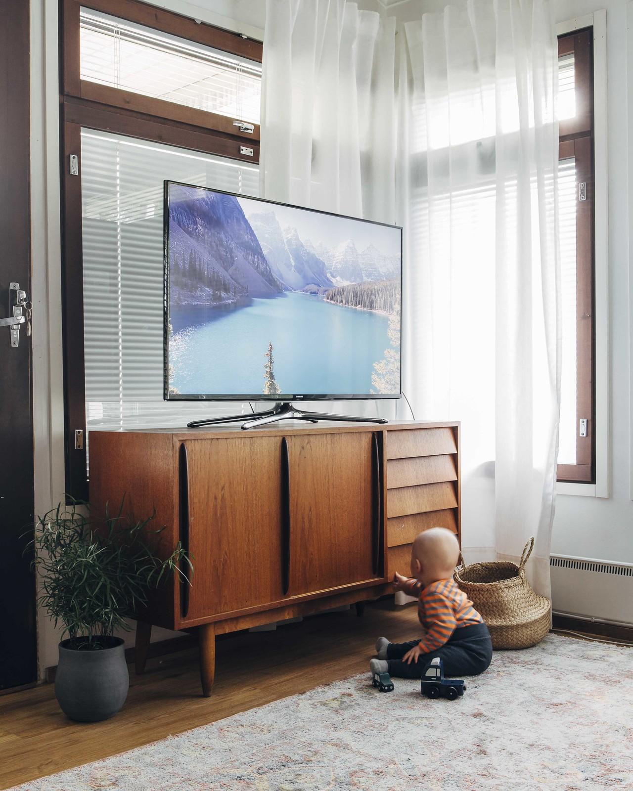 50-luvun vintage senkki, jonka päällä on televisio. Senkin edessä on lapsi, joka kokeilee yhtä vetolaatikkoa.