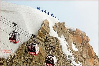Depart de l ' l'Aiguille du midi des télécabines allant  au  Helbronner  et Depart d 'une des nombreuses cordées pour une rando sur glaciers