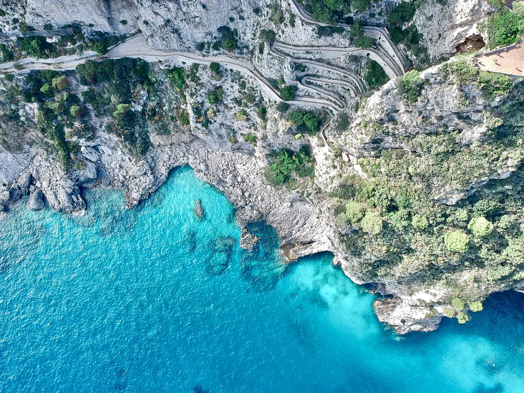 A drone view of a windy road going down the cliffs, and the turqoise colored water below