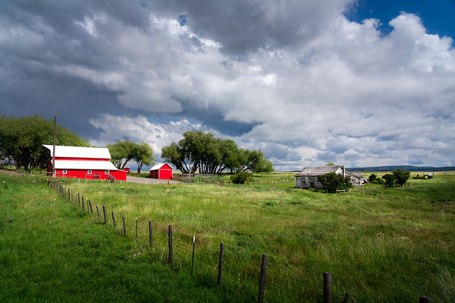small western or monitor red barn with hay hood, dramatic clouds, horses, Wallowa valley, Oregon