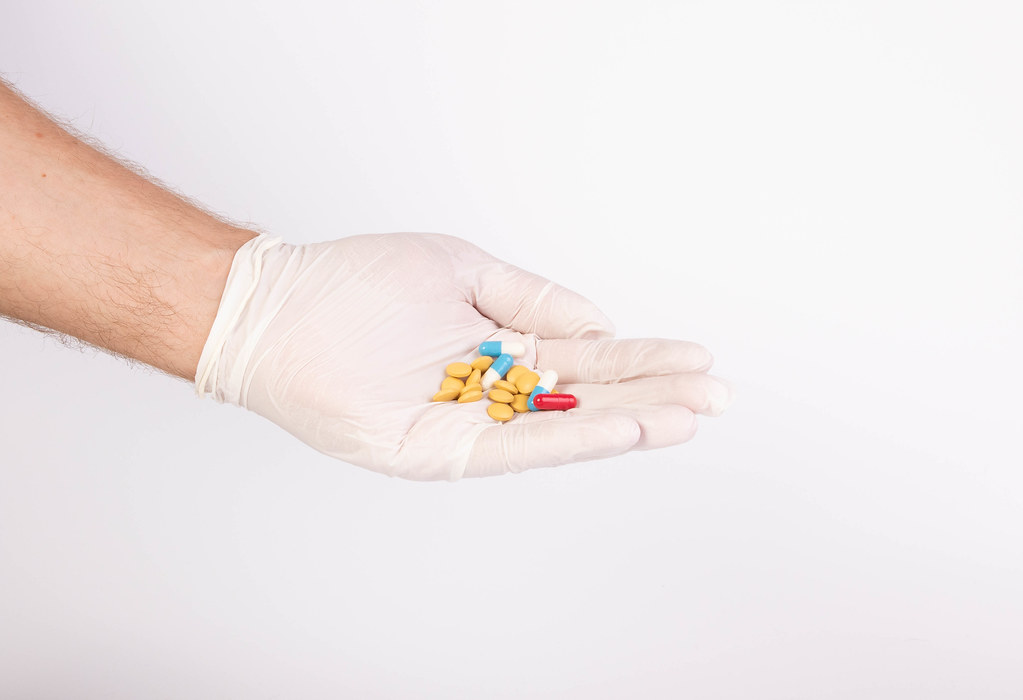 Hand with gloves holding colorful pills
