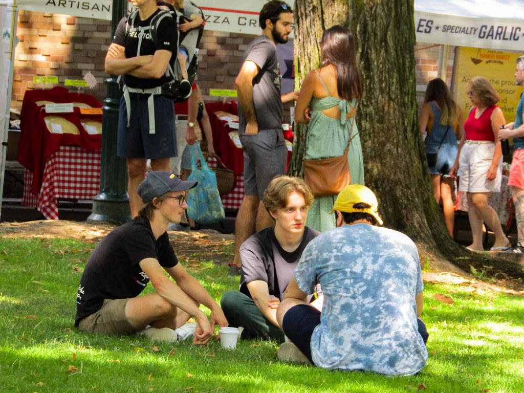 芝生に座り会話をする若者
