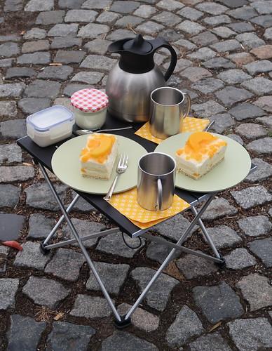 Kaffee und Pfirsich-Käsekuchen (auf Picknicktisch)
