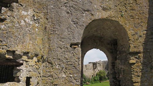 An arch framing a view of the inside courtyard of the Manorbier Castle ruins in Wales