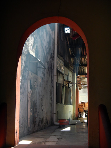 A archway leading into a sunlit Temple in Melaka, Malaysia