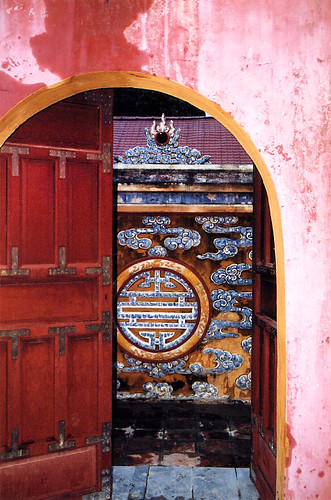 A red double-arched door gives a glimpse into the royal palace in Hue, Vietnam