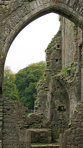 A view through the arched opening in the ruined stone walls of Cashel Hore Abbey in Ireland