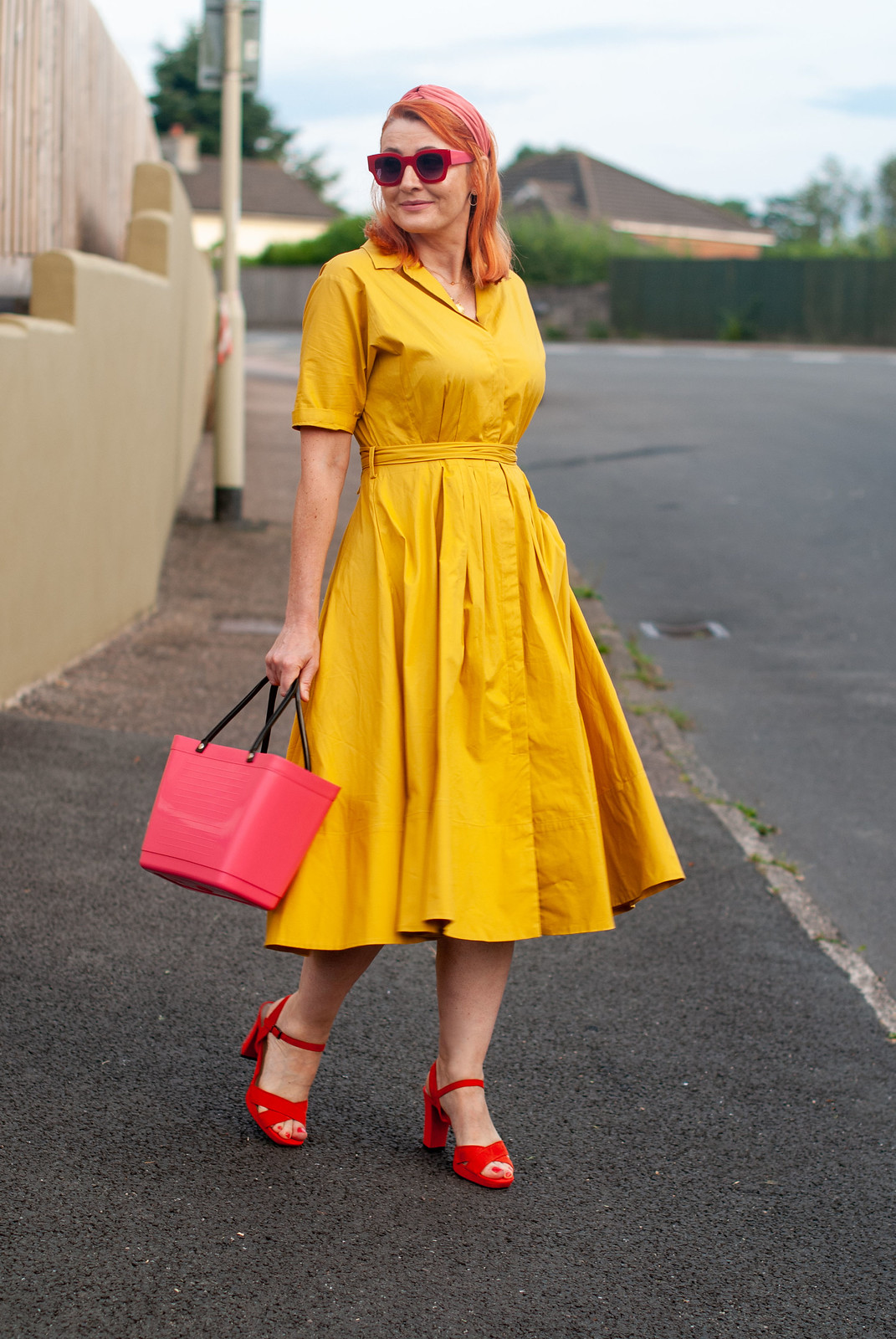 Over 40 fashion blogger Not Dressed As Lamb wearing a yellow summer dress in a shirt style \ red strappy block heels \ pink bucket bag \ pink headband \ red square sunglasses