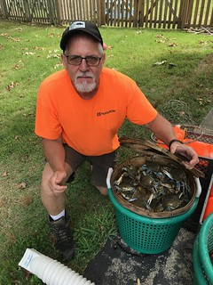 Photo of man with bushel of blue crabs