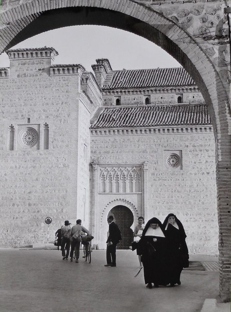 Unas monjas cruzan bajo el arco junto a la Puerta de Bisagra con Santiago del Arrabal al fondo en Toledo en 1964. Fotografía de Anno Wilms © Stiftung Anno Wilms, Berlin