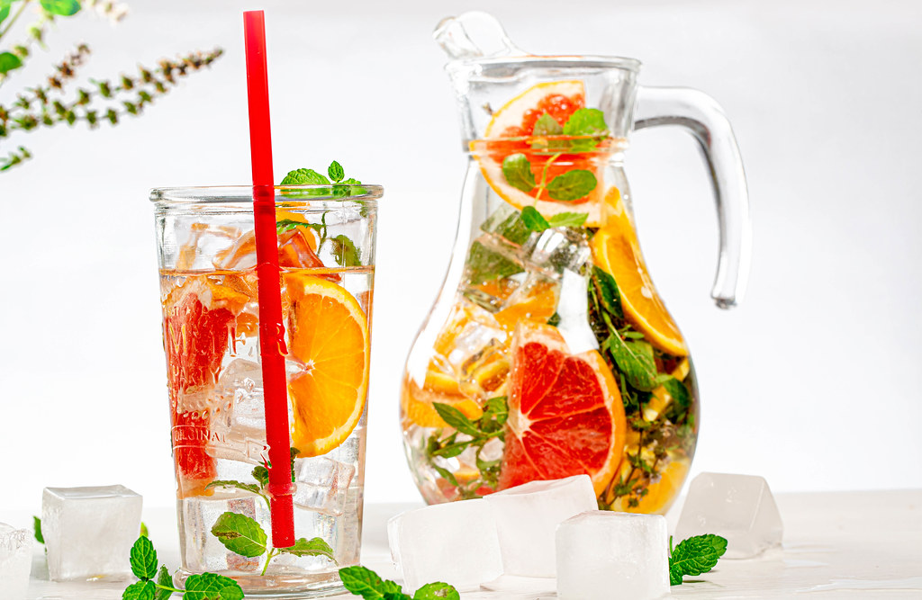 Glass and jug with a cold summer drink of mint, orange, grapefruit and lemon