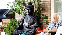 A man in Zwanenburg: in his garden with Buddha .