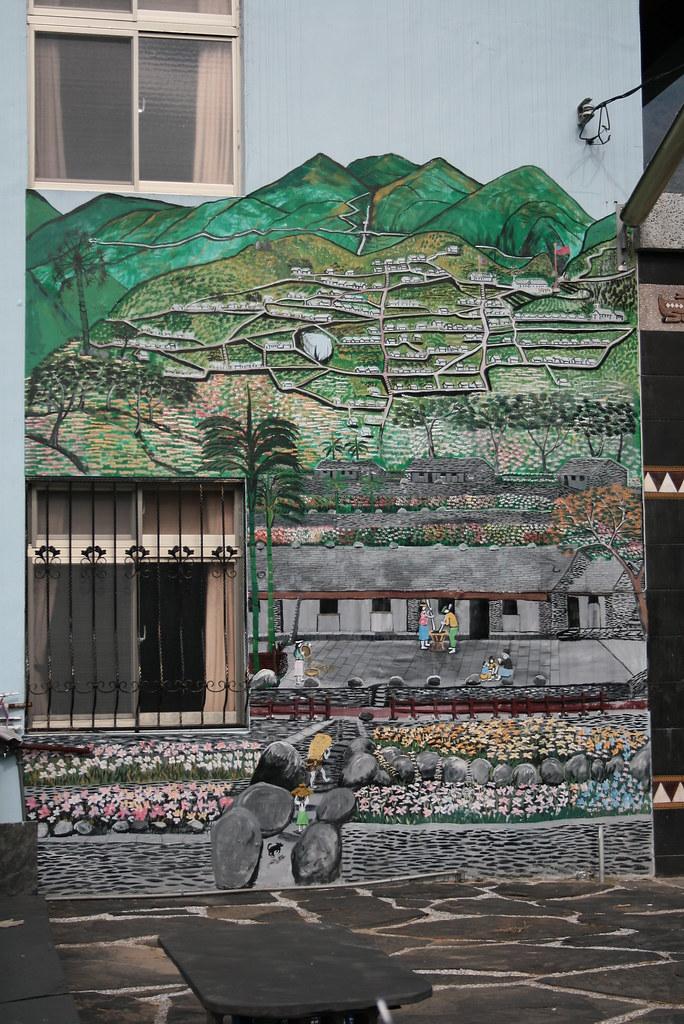 在百年山林開發和氣候變遷的雙重威脅下,山區的原住民部落正面臨巨大的生存挑戰。新好茶村已被土石流淹沒?連同這張家屋牆上的壁畫。(李根政攝於李金龍家、盧啟村畫)   p.16
