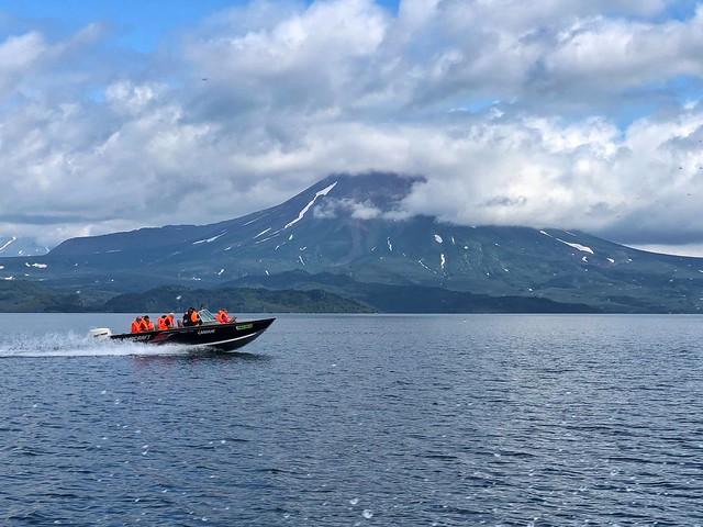 Navengando en lancha por el lago Kuril (Kamchatka) con un volcán de fondo