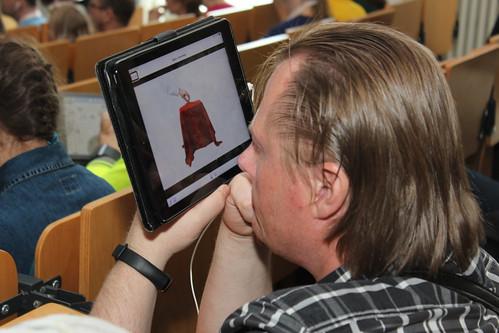 Účastník plenární sekce sleduje promítanou prezentaci na tabletu