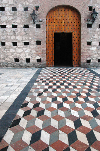 A checkered walkway leads up to an arched door in Rosario, Argentina