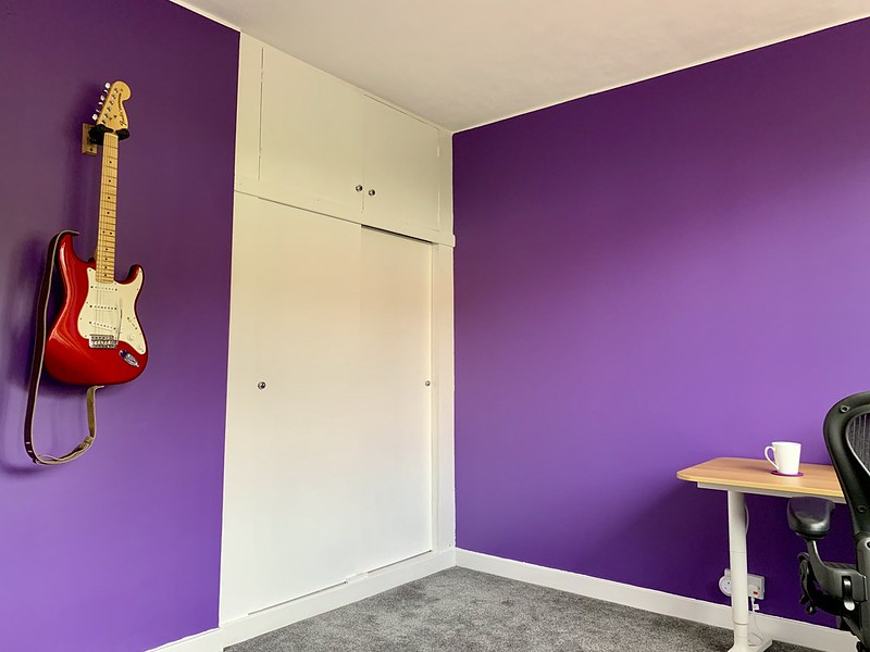 Guitar mounted on the wall. It's a candy apple red Fender Stratocaster, maple neck. The built-in cupboards are visible beside it.