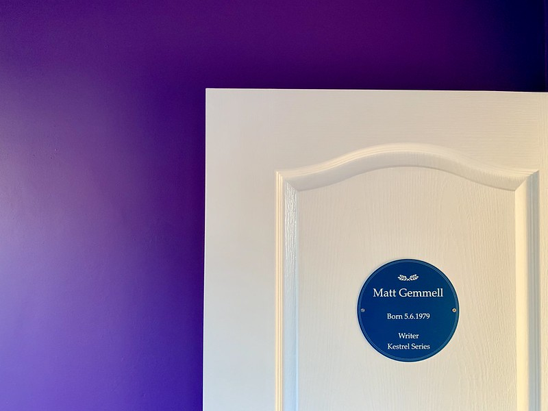 Room door open against the wall. Outer surface holds a dark blue circular plaque bearing my name, birth date, and indicating I'm the author of the KESTREL novels series.